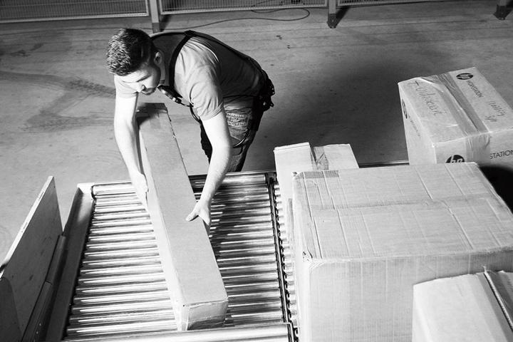 写真:重いものを持ち上げる作業をする人の姿